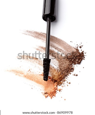close up of black mascara and face powder on white background
