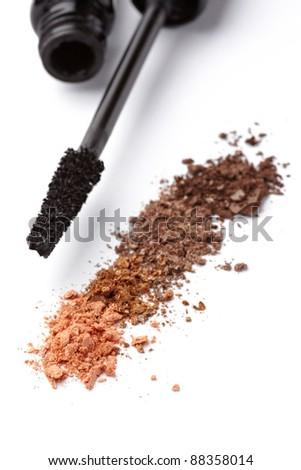 close up of black mascara and face powder on white background