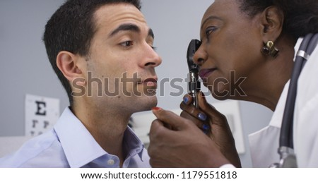 Close up of black medical doctor using retinoscope to check patients eyes