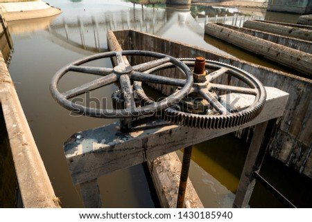 "Close-up of black metal cogwheel controlling floodgate with texts in Thai language meaning ""the property of"" on one side and ""Royal Irrigation Department"" on the other side of both cogwheels."