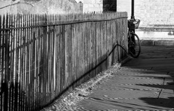 Close up of black painted railings and their shadows beside a pathway at St Nicholas Church, Chiswick, London UK, photographed with high contrast in late afternoon on a sunny day in February.