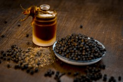 Close up of black peppercorns or kali mari on wooden surface with its extracted herbal beneficial oil.
