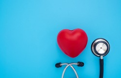 Close-up of Black stethoscope with red heart of doctor for checkup on blue background. Stethoscope equipment of medical use to diagnose hear sound. Health care and cardiology concept with copy