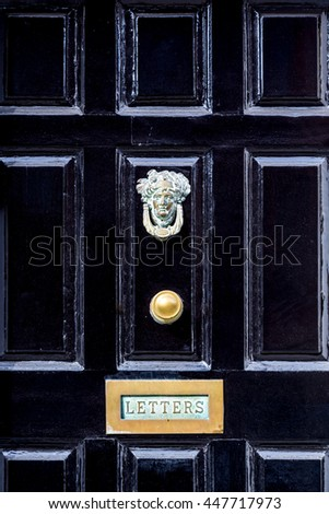 Close up of black wooden entrance door with brass letterbox in traditional style, Dublin Ireland.  #447717973