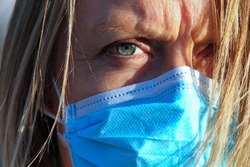 Close up of blonde woman with blue eyes with face mask, frowning expression.