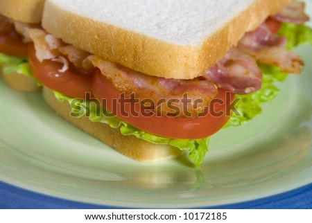Close up of BLT sandwich framed on a green and blue plate