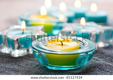 Stock Photo Close-up of blue and yellow Christmas candles on silver sand