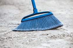 Close up of blue broom brushing grey crumbled concrete sidewalk outdoors, cleaning