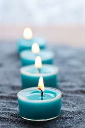 Close-up of blue candles on silver sand