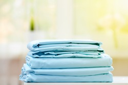 Close-up of blue clean bedding on a blurred background. A stack of folded new bed sheets on the table. Sunlight from the window.