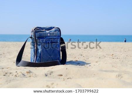 Close-up of blue denim bag with black strap on sandy beach against blue sky Stock foto ©