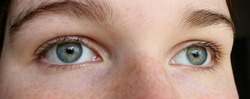 Close up of blue-green eyes of a beautiful young woman. Aquamarine colored eyes with dark lashes are calm but expressive. The young lady has smooth, clear skin. The irises are  cool and bright.