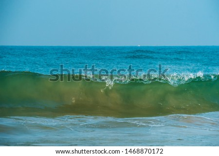 Close up of blue, green sea waves isolated in blue background. Morning with clear outdoor sky picture of shining foamy ocean high tide waters in summer, tropical beach vacation design template.