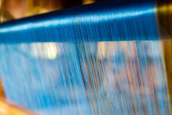 Close Up of Blue Silk on the Weaving machine and Thai traditional Silk. Weaving loom for homemade Silk textile production in Thailand