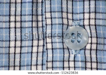 Close-up of blue squared shirt with button
