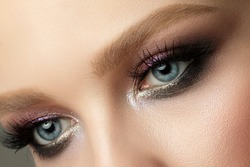 Close up of blue woman eye with beautiful brown with red and orange shades smokey eyes makeup. Modern fashion make up. Studio shot