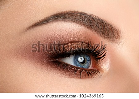 Close up of blue woman eye with beautiful brown with red and orange shades smokey eyes makeup. Modern fashion make up. #1024369165