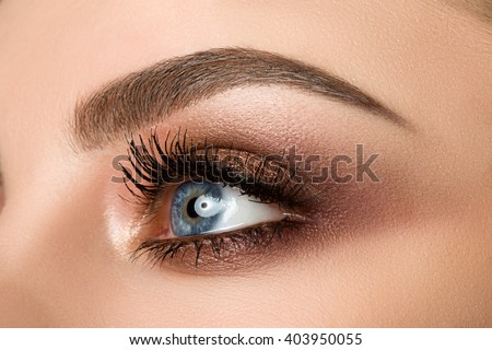 Stock Photo Close up of blue woman eye with beautiful brown with red and orange shades smokey eyes makeup. Modern fashion make up.