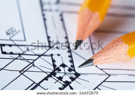 Close-up of blueprints with sketch of project on workplace and two pencils