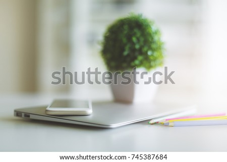 Close up of blurry office desk top with laptop, smartphone, colorful pencils and decorative green plant