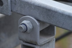 Close up of boat trailer gray galvanized support beam, clamp with bolt and lock nut and blurred green-like background from another angle