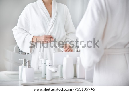 Close up of body of young woman tying up belt of white bathrobe in front of the mirror