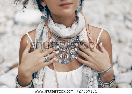 close up of boho styled woman on tropical beach with white pebble #727359175