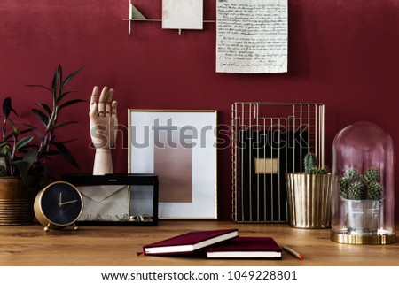 Close-up of books, gold clock, poster and cacti on desk in workspace interior with red wall