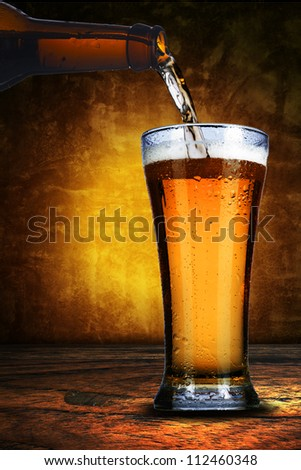Close up of bottle of beer pure into a glass. Cold refreshment