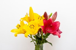 Close-up of Bouquet of red and yellow lily flowers in a glass vase