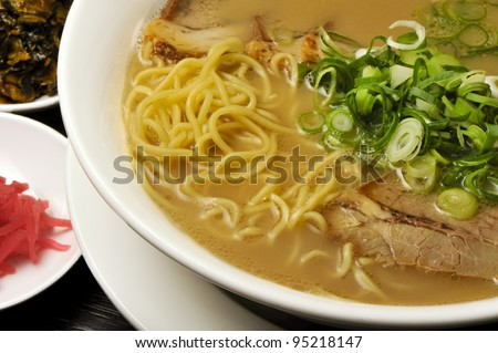 close up of bowl of japanese ramen with pickles on the side