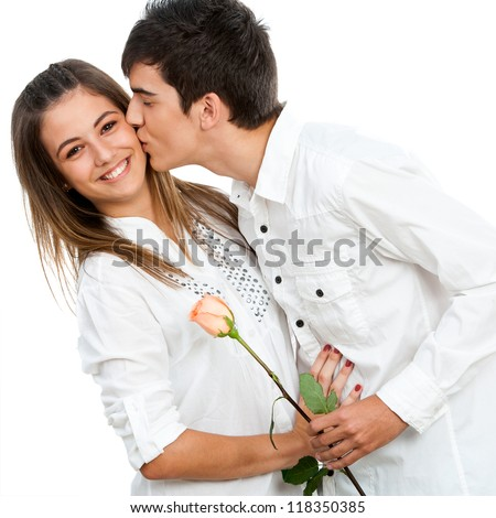 Close up of boy giving girlfriend a rose and romantic kiss.Isolated.