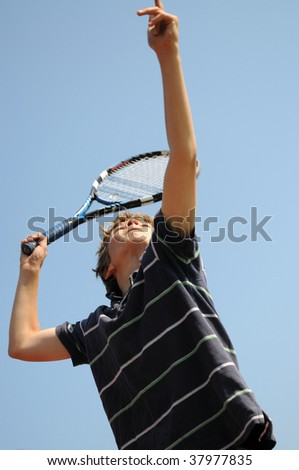 close up of boy playing tennis