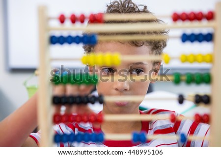 Close-up of boy playing with abacus in classroom #448995106