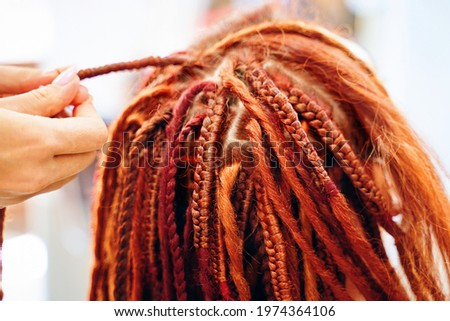 Close up of braiding process plait with colored kanekalon. Beauty salon services. Girl hairdresser weaves woman ginger dreadlocks. Stylish therapy professional care concept. Hippie style hairstyle. Stock foto ©
