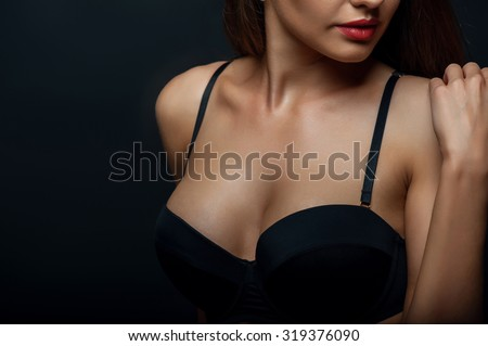 Close up of breast of attractive woman presenting her black bra. She is touching her shoulder gently. Isolated on black background and there is copy space in left side