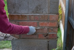 close up of bricklayer hand laying bricks and pointing up mortar bed with gagger tool , building a barbecue outside in autumn