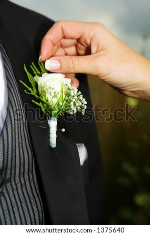 Close-up of Bridal accessories. Hand of bride fixing a Corsage.
