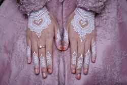 Close-up of bride hand with floral design white henna and wedding rings.