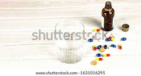 Close-up of bright colored medical tablets, a bottle of medicine and capsules with medicines and a glass of water. Scattered on the table Pills from the first-aid kit box. Banner