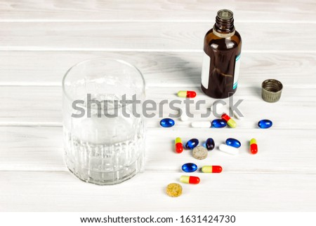 Close-up of bright colored medical tablets, a bottle of medicine and capsules with medicines and a glass of water. Scattered on the table Pills from the first-aid kit box. Toned. Copy space