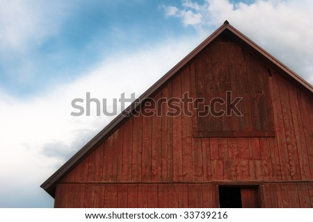Close-up of bright red barn roof against cloudy blue sky