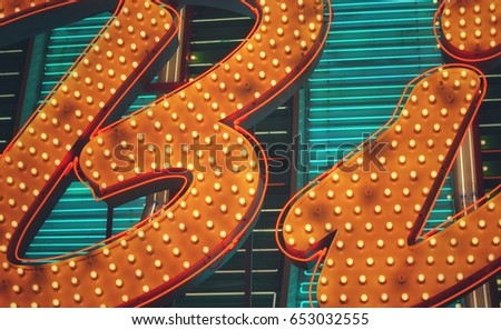 Close up of bright yellow and blue neon light letters on a sign. #653032555