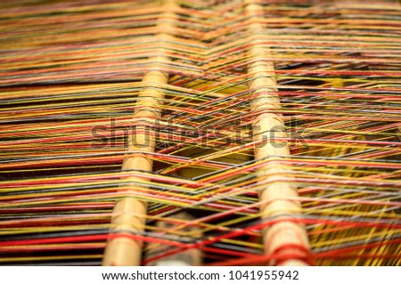 Close up of brocade fabric weaving on loom, cotton on the manual wood loom in Vietnam traditional culture
