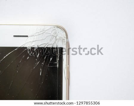 Close up of broken glass and cracked display or screen of mobile phone or smartphone on white background.