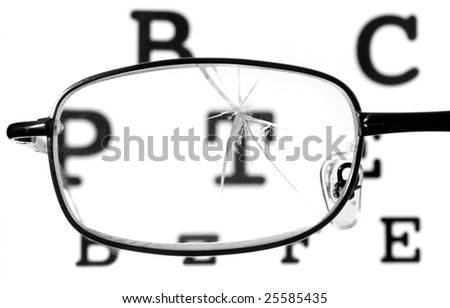 close up of broken glasses and snellen chart