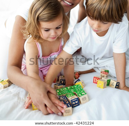 Close-up of brother and sister playing with cube toys on the bed