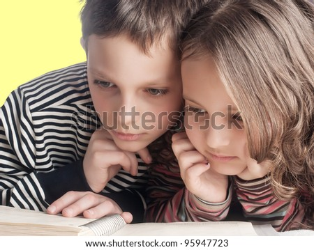 close up of  brother and sister reading a book, on the bed