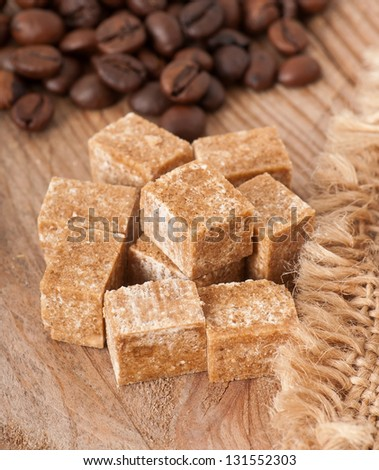 Close up of brown sugar cubes and coffee beans