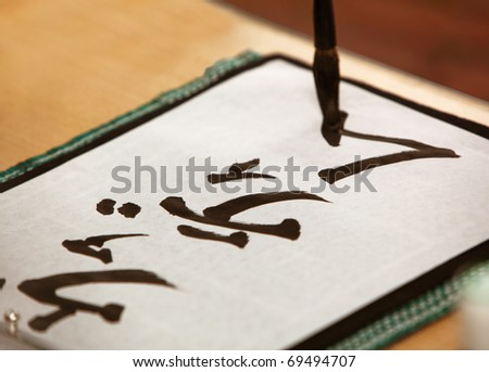 Close up of brush writing Japanese characters - stock photo